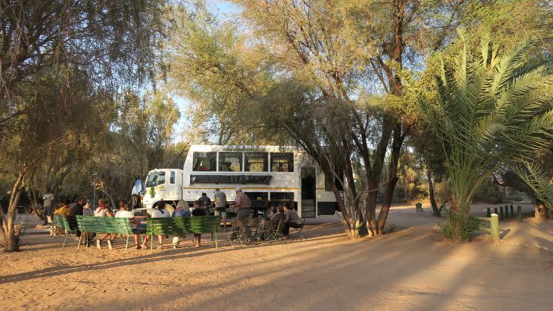 Reisegruppe sitzt vor ihrem Truck