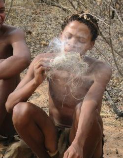 Ein San in Botswana beim Feuermachen