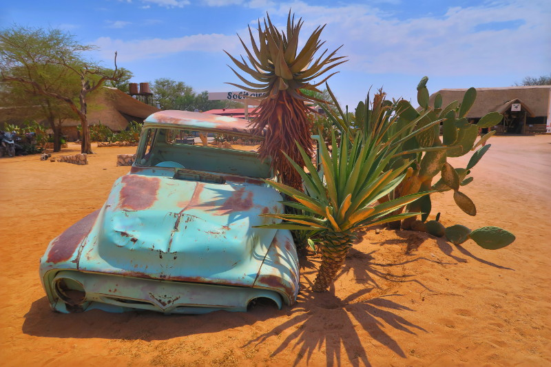 Altes Auto im Sand am Eingang der Ministadt Solitaire in Namibia
