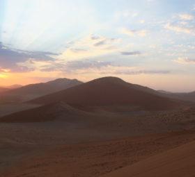 Hinter den Dünen in der Namibwüste geht die Sonne auf