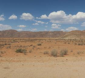 Irgendwo in Namibia: blauer Himmel und weiße Wölkchen über der trockenen Steppe mit Bergen im Hintergrund