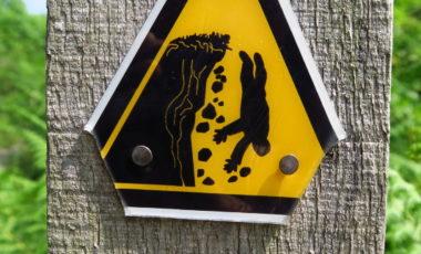 Achtung, steil: ein schwarz-gelbes Warnschild an einem Wanderweg in Pembrokeshire