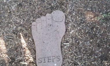 Ein Fuß aus Stein mit der Aufschrift Steps
